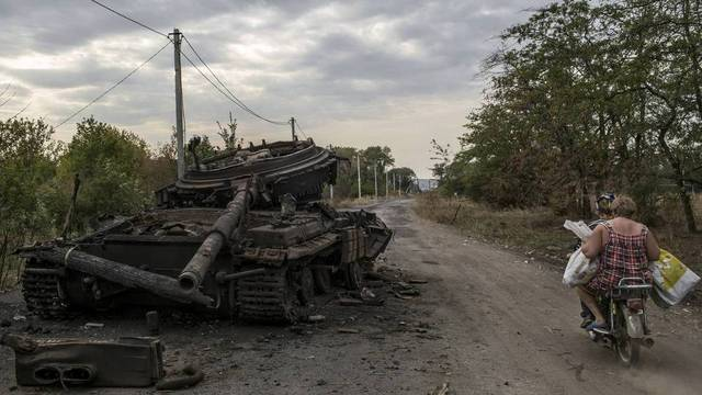 Women ride past a burned out Ukrainian tank in the town of Ilovaysk Photo: MAURICIO LIMA | Agência O Globo