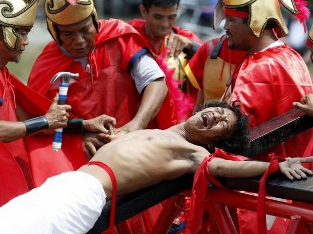 Гвозди пронзают руки распятого мужчины в страстную пятницу на Филиппинах (AP Photo/Bullit Marquez)