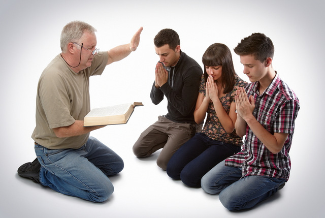 Preacher leading three young souls in prayer to receive Jesus